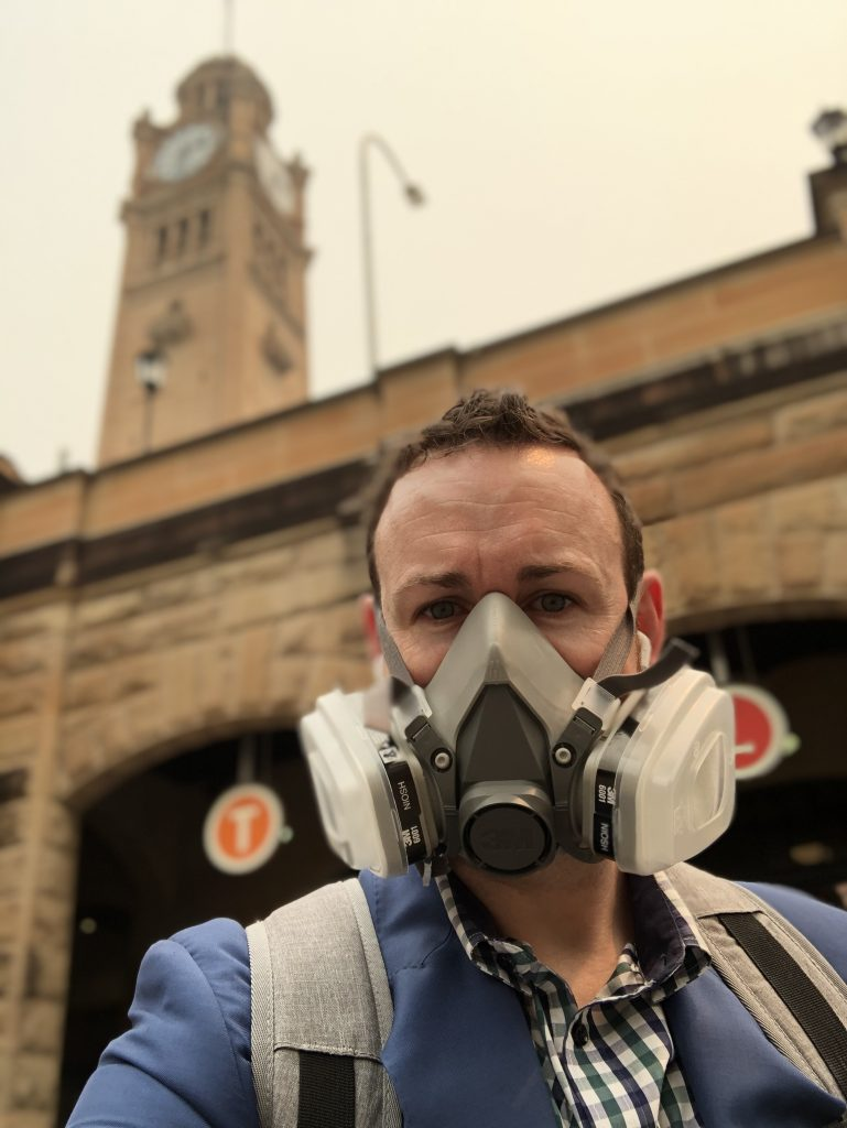 Richard in an industrial looking mask that filters out PM2.5 particles due to the smoke haze in Sydney.